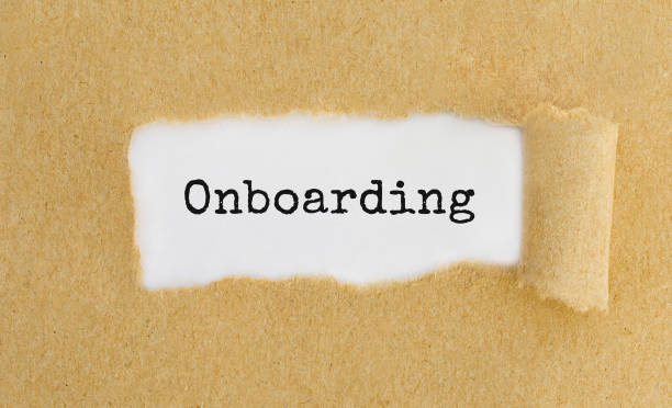 Text ONBOARDING appearing behind ripped brown paper stock photo