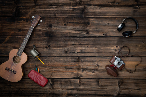 istock Text or logo empty copy space in vertical top view dark vintage wood.Retro sharpener,guitar ukulele,camera,headphones.Winter holiday season party social media card background 1058881376