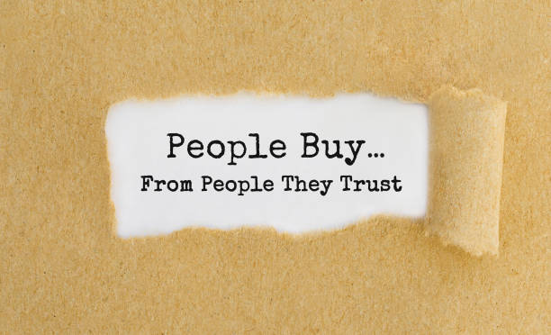 Text People Buy From People They Trust appearing behind ripped brown paper. Text People Buy From People They Trust appearing behind ripped brown paper. buy single word stock pictures, royalty-free photos & images