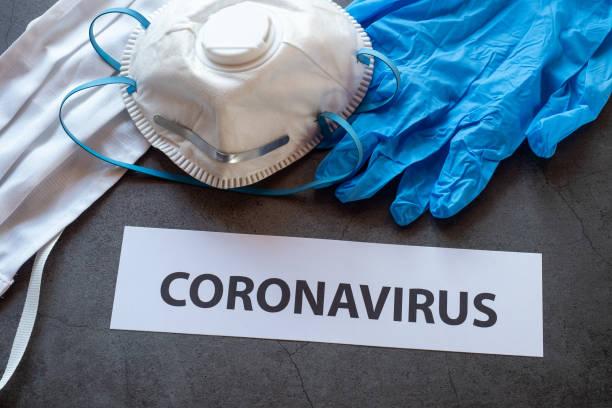 Textphrase Coronavirus auf schwarzem Hintergrund mit schützenden medizinischen Masken, Handschuhen und Atemschutzmasken FFP2 für Coronavirus-Epidemie. – Foto