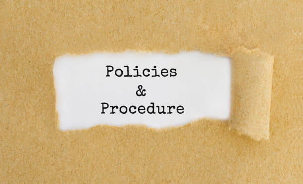Text Policies and Procedure appearing behind ripped brown paper. stock photo