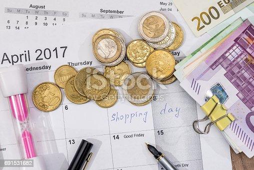 text shopping day write on calendar with euro banknotes, coin, pen.