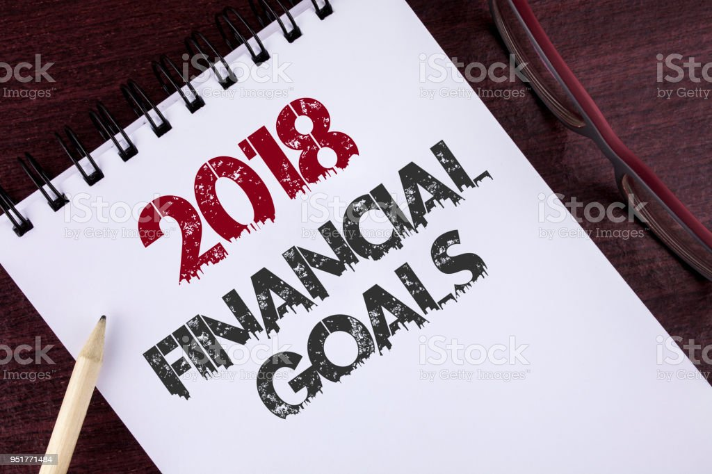 Text sign showing 2018 Financial Goals. Conceptual photo New business strategy earn more profits less investment written on Notepad on the Wooden background Pencil and Glasses next to it. stock photo