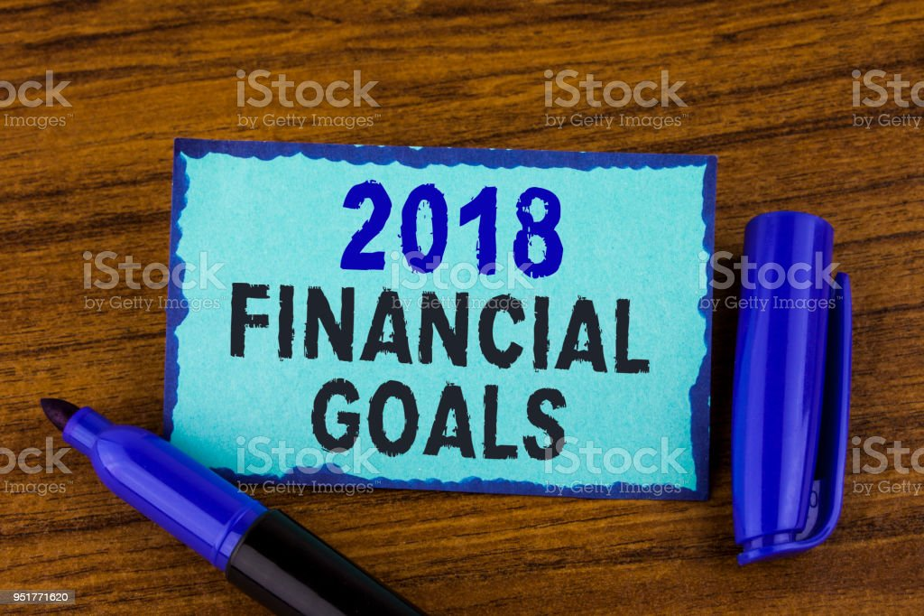Text sign showing 2018 Financial Goals. Conceptual photo New business strategy earn more profits less investment written on Sticky Note paper on the wooden background Marker next to it. stock photo
