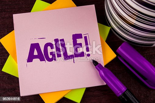 istock Text sign showing Agile Motivational Call. Conceptual photo Develop an agility towards technological chnage written on Sticky note paper on wooden background Marker and Cup next to it. 952644816