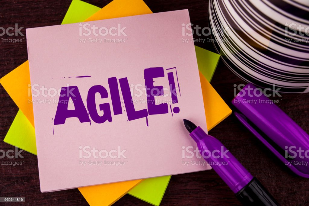 Text sign showing Agile Motivational Call. Conceptual photo Develop an agility towards technological chnage written on Sticky note paper on wooden background Marker and Cup next to it. stock photo