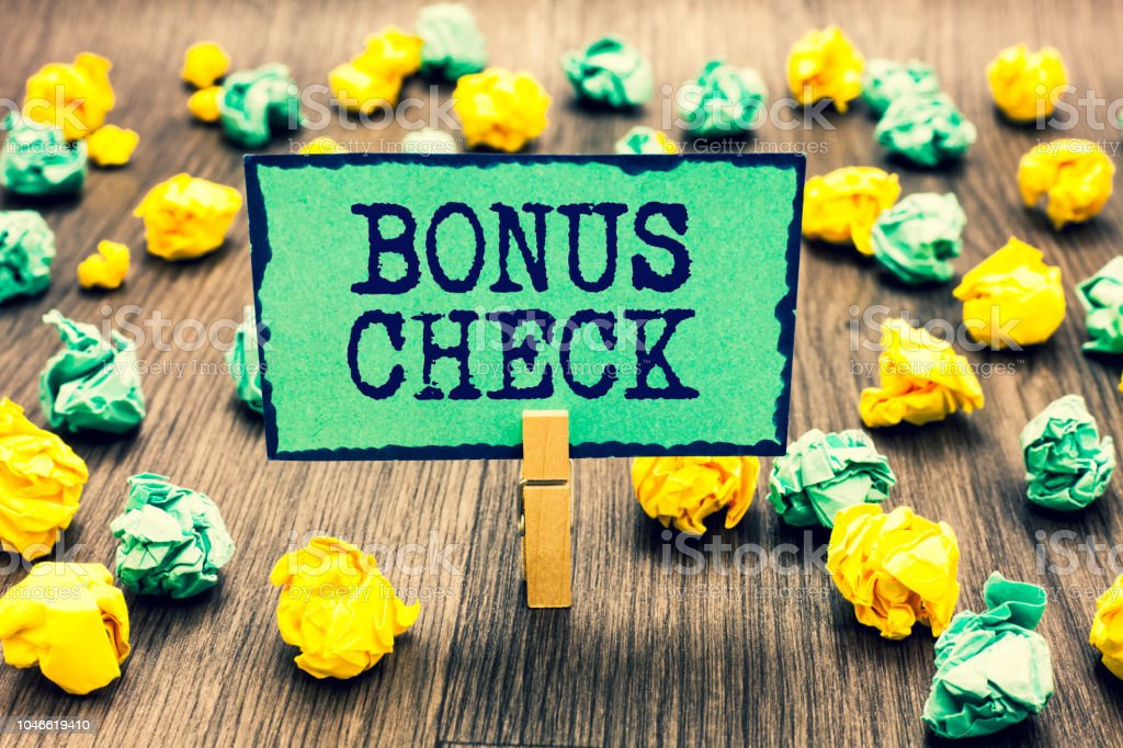 Text sign showing Bonus Check. Conceptual photo something in addition to what is expected or strictly due Clothespin holding green note paper crumpled papers several tries mistakes. stock photo