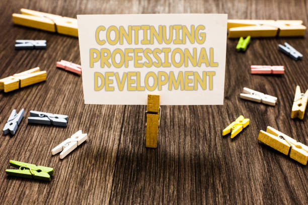 Text sign showing Continuing Professional Development. Conceptual photo tracking and documenting knowledge Clothespin holding white paper note several clothespins wooden floor. stock photo