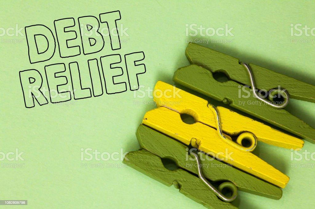 Text-Schild mit Schuldenerlass. Konzeptuelle Foto teilweise oder totale Remission davon insbesondere durch drei Länder grün gelb Oldtimer Wäscheklammern klaren Hintergrund Holding Dinge. – Foto
