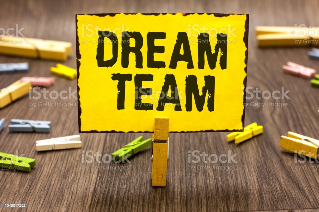 Text sign showing Dream Team. Conceptual photo Prefered unit or group that make the best out of a person Clothespin holding yellow paper note several clothespins wooden floor. stock photo