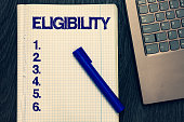 Text sign showing Eligibility. Conceptual photo State of having the right for doing or obtain something Proper Open notebook squared page black marker computer keyboard wooden background.