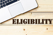 Text sign showing Eligibility on wooden table