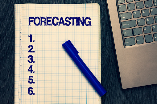 istock Text sign showing Forecasting. Conceptual photo Predict Estimate a future event or trend based on present data Open notebook squared page black marker computer keyboard wooden background. 1049733476