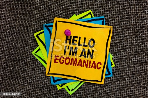 Text sign showing Hello I am An Egomaniac. Conceptual photo Selfish Egocentric Narcissist Self-centered Ego Black bordered different color sticky note stick together with pin on jute sack