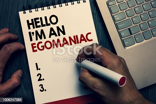 Text sign showing Hello I am An Egomaniac. Conceptual photo Selfish Egocentric Narcissist Self-centered Ego Written words and number on notepad man hold marker keyboard on wooden desk