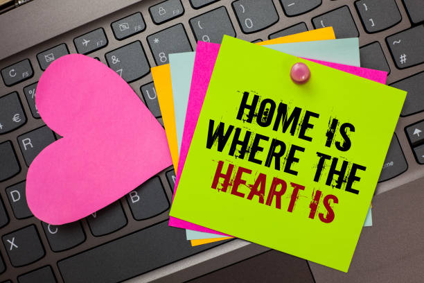 Text sign showing Home Is When The Heart Is. Conceptual photo Your house is where you feel comfortable and happy Bright colorful written papers pinch by pin pink heart on computer keyboard. stock photo