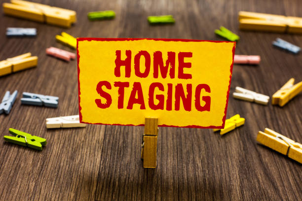 Text sign showing Home Staging. Conceptual photo Act of preparing a private residence for sale in the market Clothespin holding yellow paper note several clothespins wooden floor stock photo