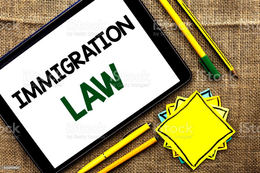 Text sign showing Immigration Law. Conceptual photo National Regulations for immigrants Deportation rules written on Tablet on the jute background Pens Pencil and Sticky Note Papers stock photo