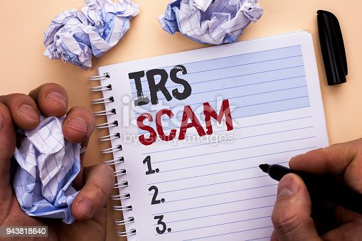 istock Text sign showing Irs Scam. Conceptual photo Warning Scam Fraud Tax Pishing Spam Money Revenue Alert Scheme written by Man on Notebook Book holding Marker on Plain background 943818640