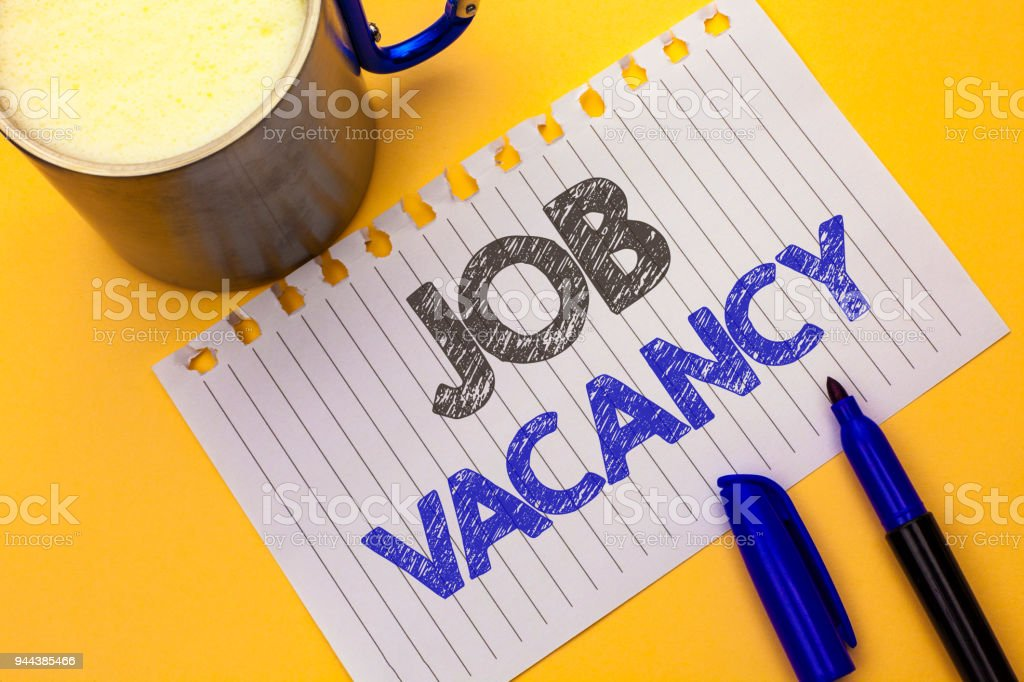 Text sign showing Job Vacancy. Conceptual photo Work Career Vacant Position Hiring Employment Recruit Job written on Notebook Paper on the plain background Coffee Cup and Marker next to it. stock photo