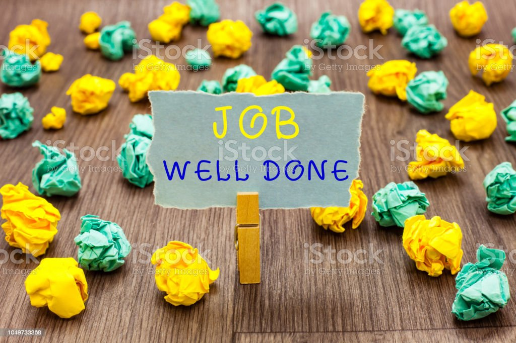 Text sign showing Job Well Done. Conceptual photo Well Performed You did it Cheers Approval Par Accomplished Clothespin holding gray note paper crumpled papers several tries mistakes. stock photo