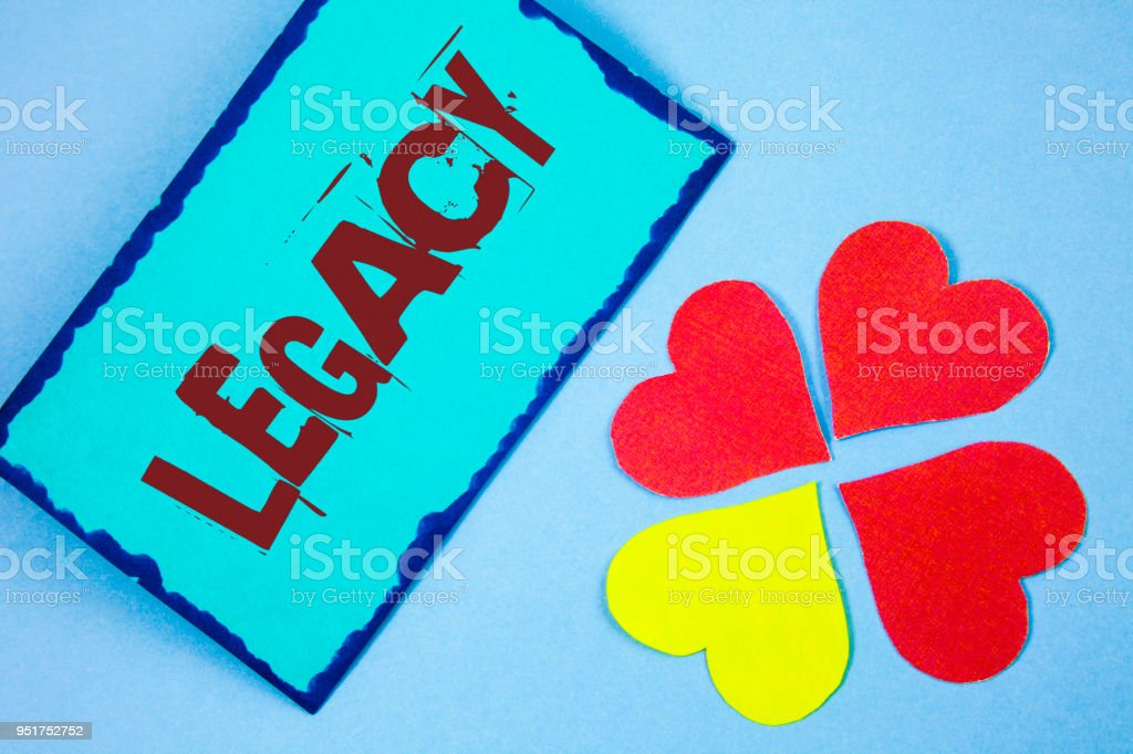 Text sign showing Legacy. Conceptual photo Transmitted Received from an ancestor Money Properties given by will written on Sticky Note paper on plain background Paper Love Hearts next to it. stock photo
