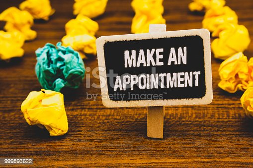 istock Text sign showing Make An Appointment. Conceptual photo Schedule Arrangement Deadline Session Engagement Blackboard with letters wooden floor blurry yellow paper lumps green lob. 999893622
