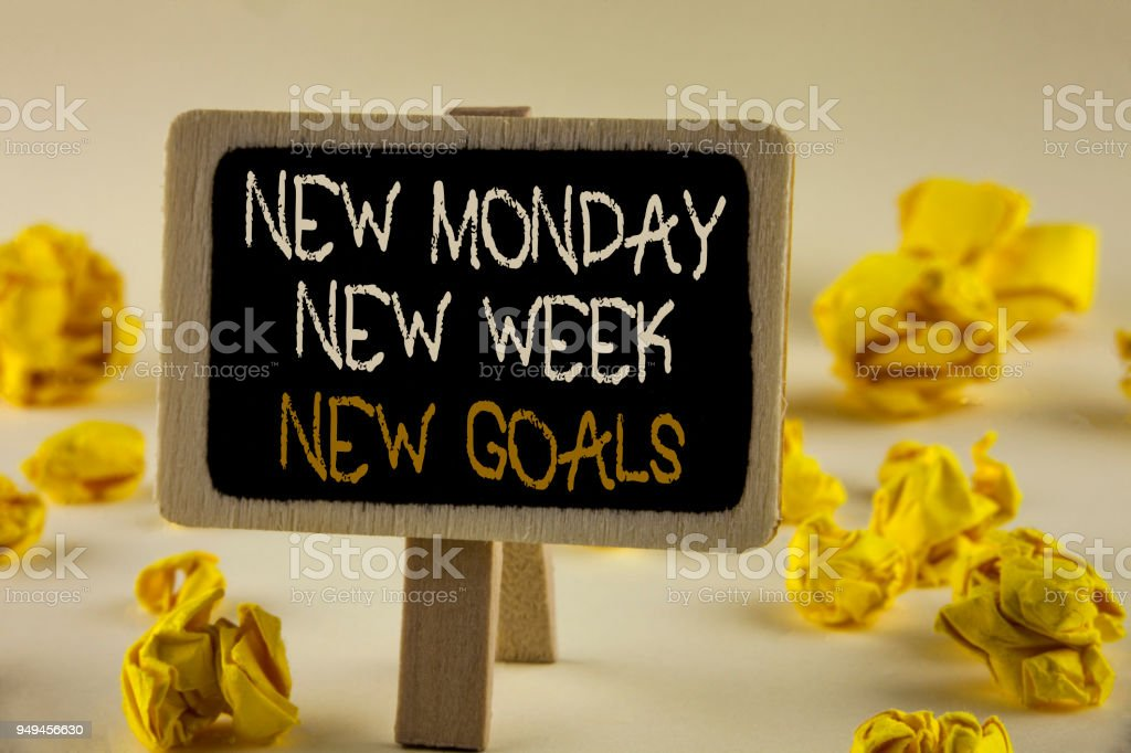 Text sign showing New Monday New Week New Goals. Conceptual photo next week resolutions To do list Goals Targets written on Wooden Notice Board on the plain background Yellow Paper Balls. stock photo