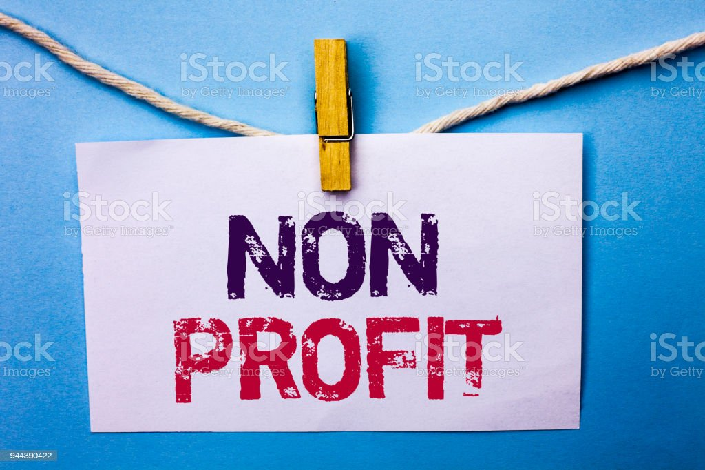 Text sign showing Non Profit. Conceptual photo Charitable Wrothless Philanthropy Aid Unlucrative Profitless written on White Note Paper hanging with rope on the plain background Clip. stock photo