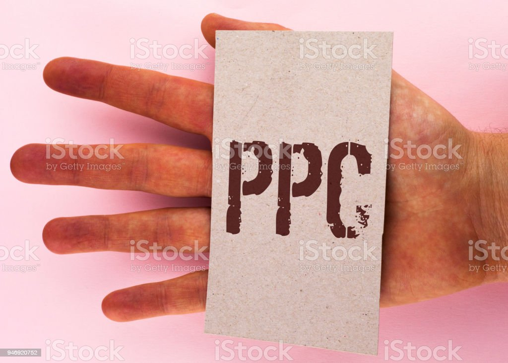 Text sign showing Ppc. Conceptual photo Pay Per Click Advertising Strategies Direct Traffic to Websites written on Cardboard Piece placed on Hand on the plain background. – zdjęcie