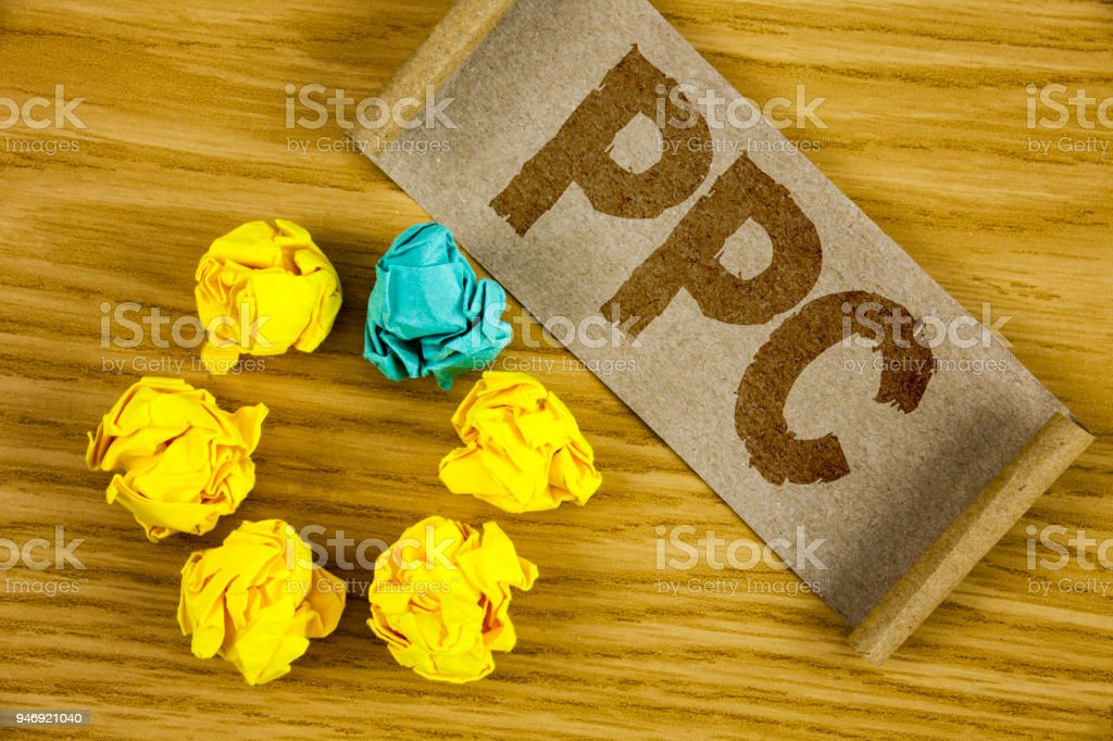 Text sign showing Ppc. Conceptual photo Pay Per Click Advertising Strategies Direct Traffic to Websites written on Folded Cardboard Paper piece on wooden background Crumpled Paper Balls. – zdjęcie