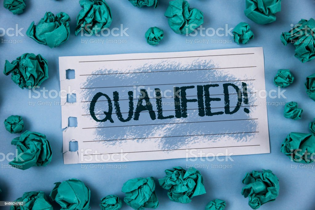 Text sign showing Qualified Motivational Call. Conceptual photo Certified to perform a job Competent Experienced written on Notepad Paper within Green Paper Balls on Plain Blue background. stock photo