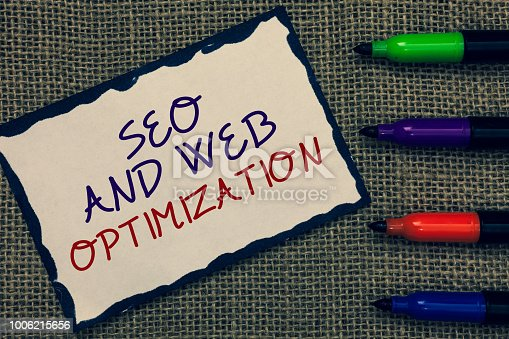 1045434476istockphoto Text sign showing Seo And Web Optimization. Conceptual photo Search Engine Keywording Marketing Strategies Blue bordered page drawn some texts laid color pen jute background. 1006215656
