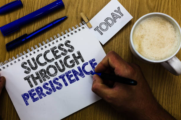 Text sign showing Success Through Persistence. Conceptual photo never give up in order to reach achieve dreams Man holding marker notebook clothespin reminder wooden table cup coffee. stock photo