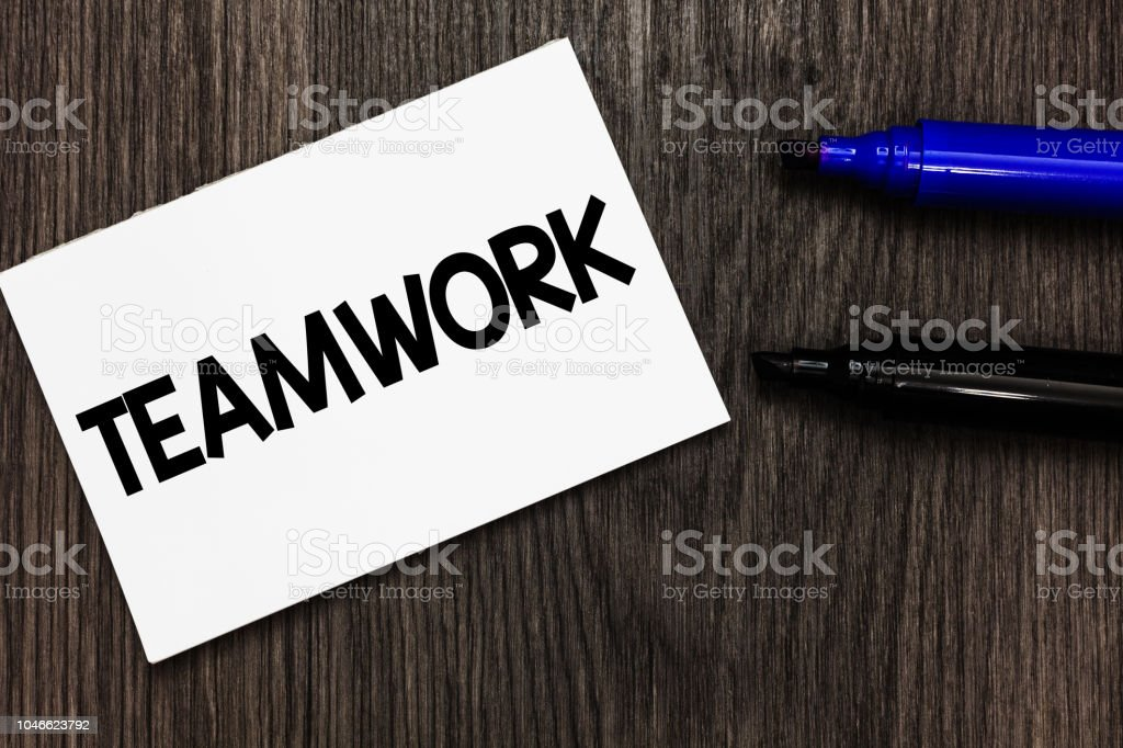 Text sign showing Teamwork. Conceptual photo Group of people who work together as one and with the same aim Important idea ideas notebook marker markers wooden background reminder. stock photo