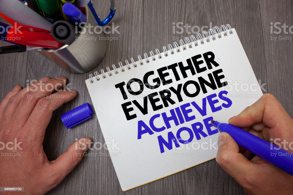 Text sign showing Together Everyone Achieves More. Conceptual photo Teamwork Cooperation Attain Acquire Success Man hold holding blue marker notebook page markers table messages ideas. stock photo