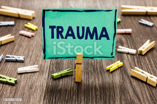 istock Text sign showing Trauma. Conceptual photo Disturbing physical and emotional injuries shock experience Random clips art work board creative nice paperclips wood grey shadow. 1003867308