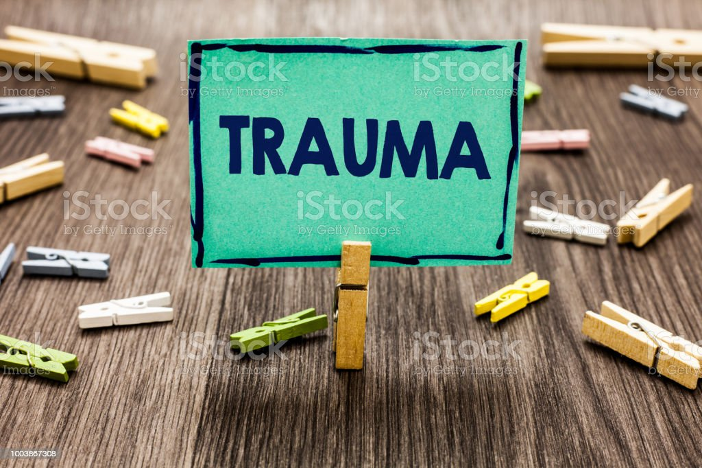 Text sign showing Trauma. Conceptual photo Disturbing physical and emotional injuries shock experience Random clips art work board creative nice paperclips wood grey shadow. stock photo