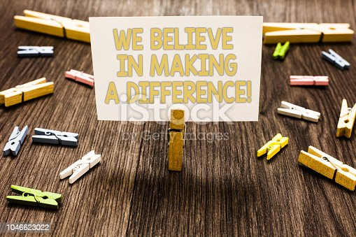 istock Text sign showing We Believe In Making A Difference. Conceptual photo self-confidence that can be unique Clothespin holding white paper note several clothespins wooden floor. 1046623022