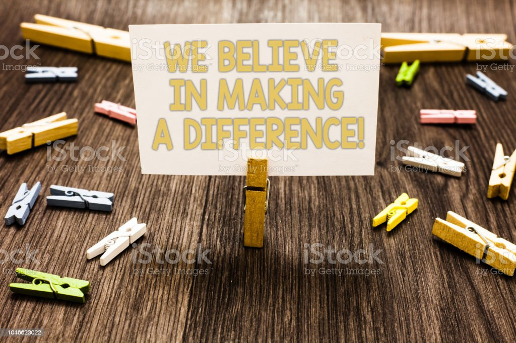 Text sign showing We Believe In Making A Difference. Conceptual photo self-confidence that can be unique Clothespin holding white paper note several clothespins wooden floor. stock photo