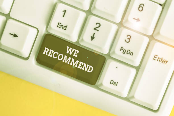 Text sign showing We Recommend. Conceptual photo suggest that someone or something would be good or suitable White pc keyboard with empty note paper above white background key copy space. stock photo