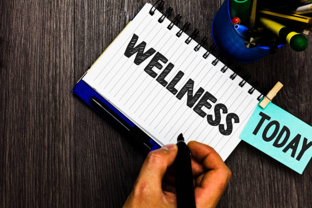 Text sign showing Wellness. Conceptual photo Making healthy choices complete mental physical relaxation Reminder appointment daily work pens penholder clip paperclip papers. stock photo