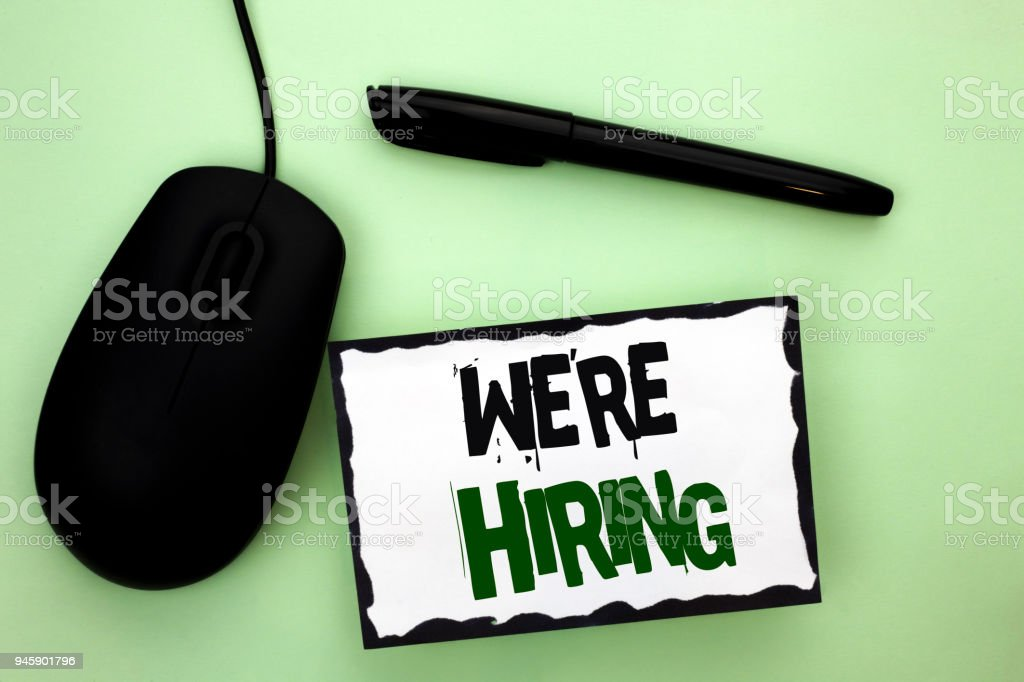Text sign showing We're Hiring. Conceptual photo Recruiting Hiring Now Recruitment Vacancy Announced Hire written on Sticky Note Paper on the plain background Pen and Mouse next to it. stock photo