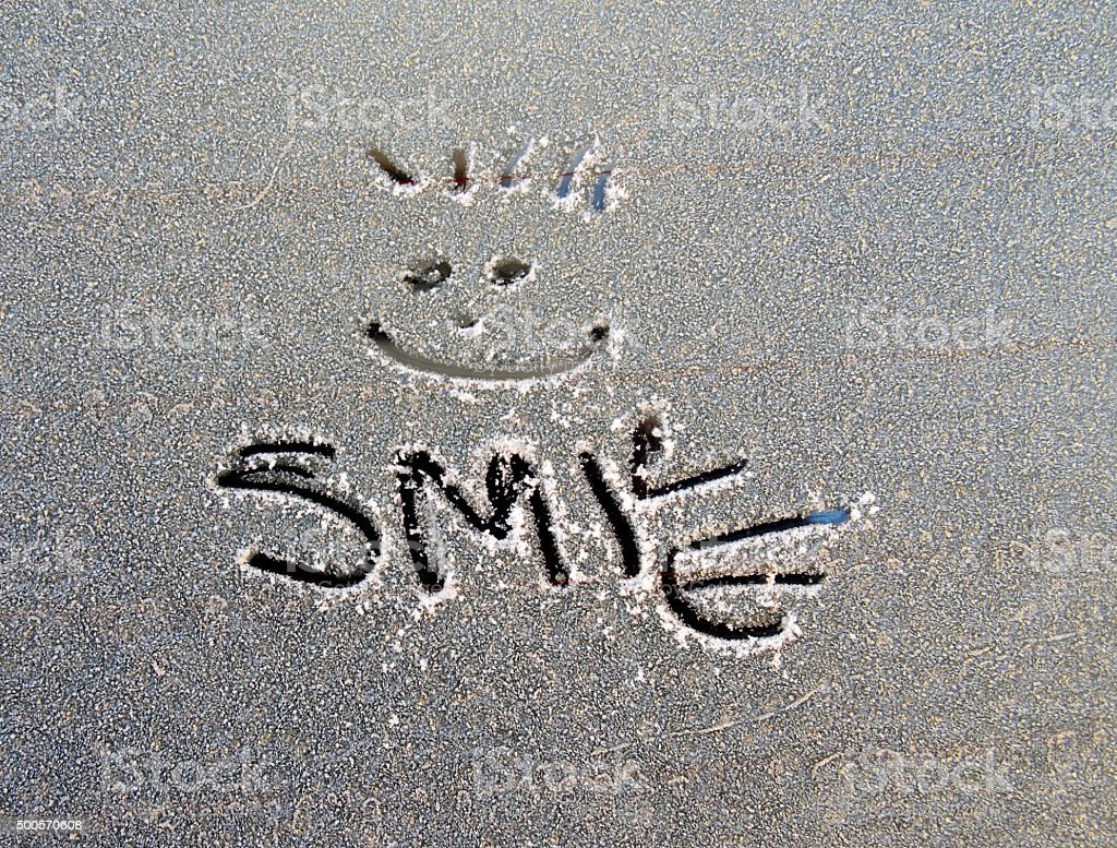 text smile  on frost car window stock photo