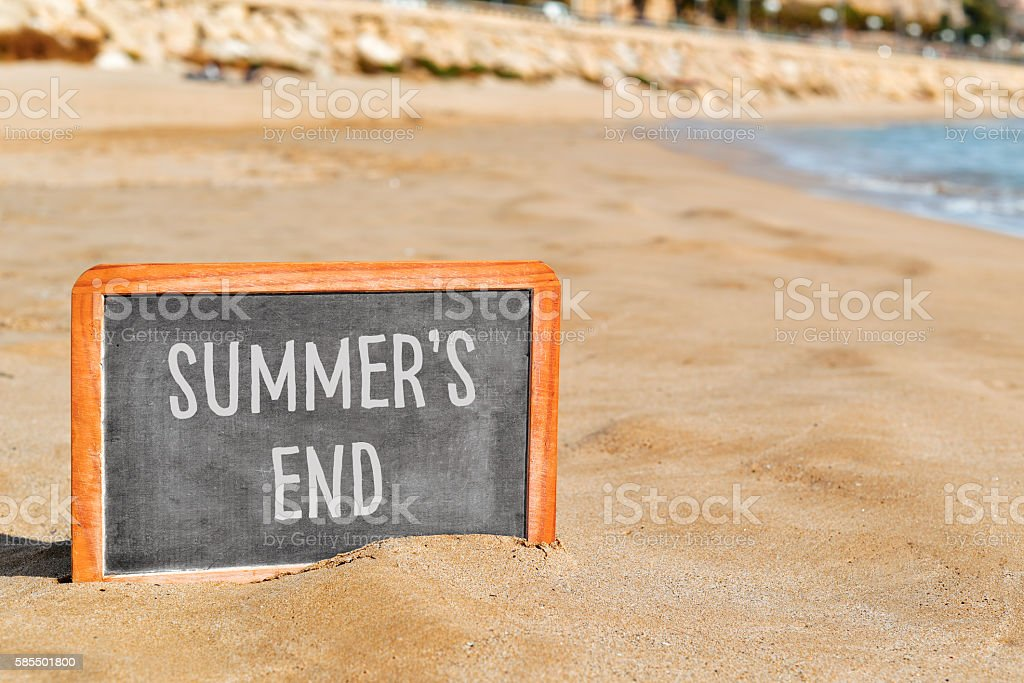 text summers end in a chalkboard on the beach stock photo
