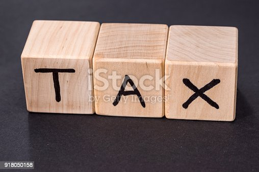 947260978 istock photo text tax on wooden cubes isolated on black 918050158
