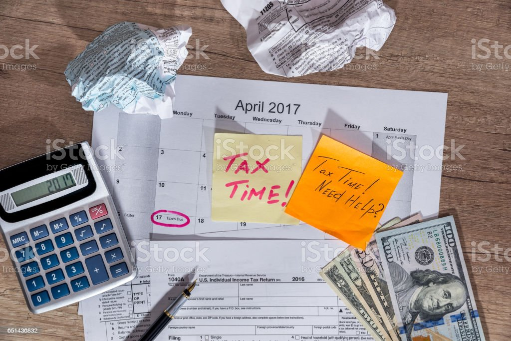 text 'tax time' on tax forms 1040 with pen, calculator and money. stock photo