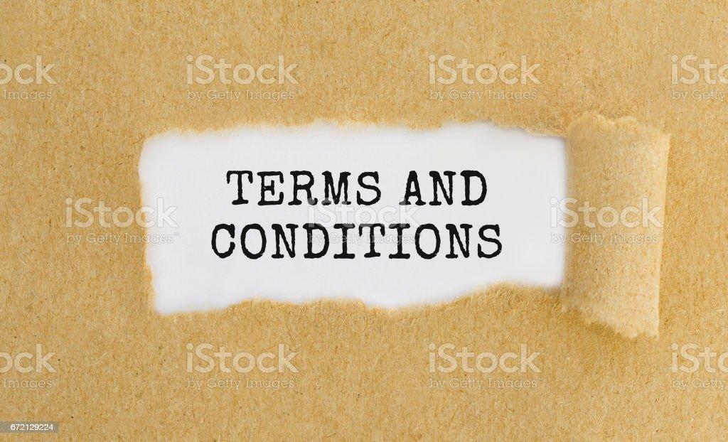 Tekst voorwaarden weergegeven achter geript bruin papier. foto
