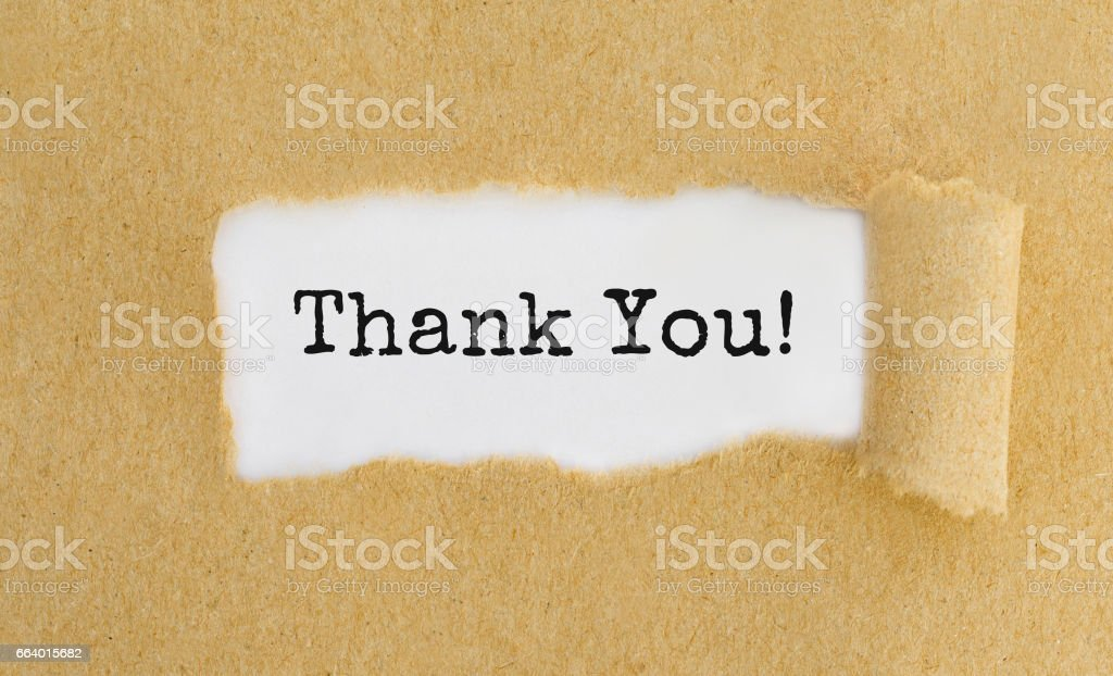 Text Thank You appearing behind ripped brown paper. stock photo