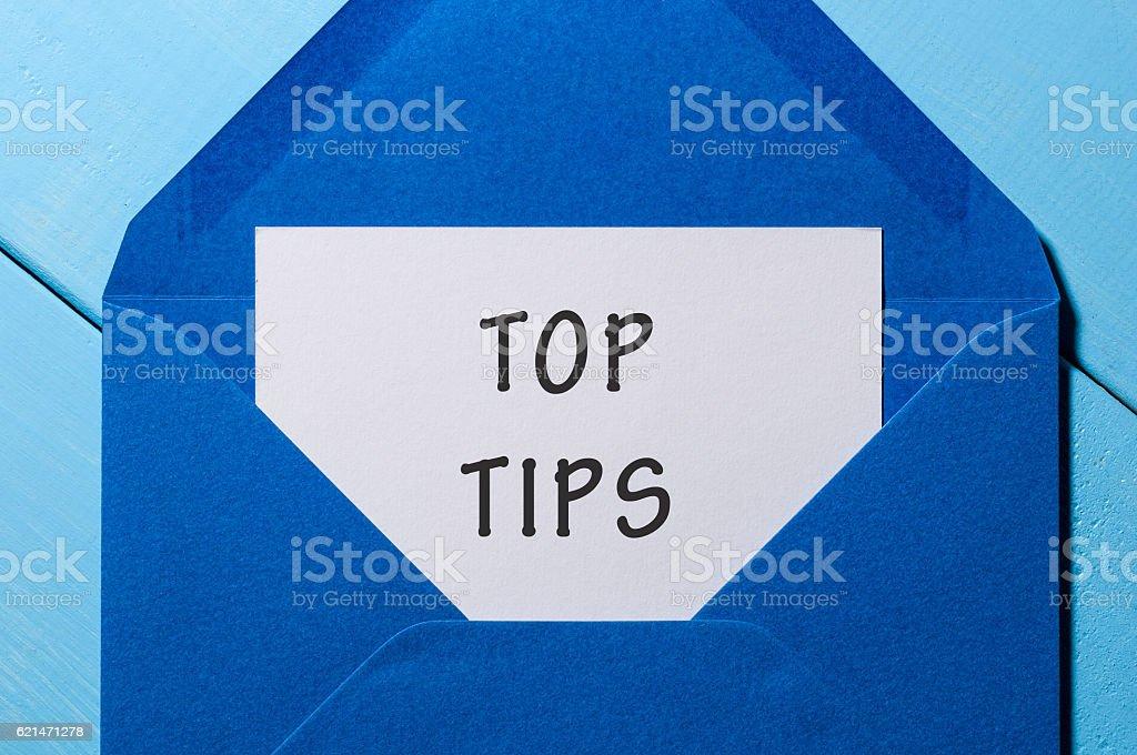 Text TOP TIPS on paper in blue envelope. Business concept stock photo